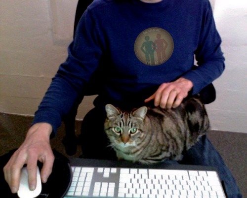Otis sits on one of the Guardians' laps.  A keyboard and mouse is in front of them.